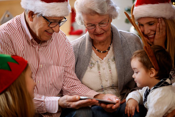 Grandparents with children looking Christmas photos on cell phone