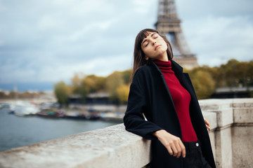 Beautiful young Parisian woman in long coat near the Eiffel tower on a autumn day Wall mural