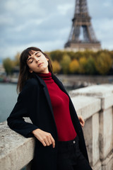 Portrait of a young stylish woman sitting on the bridge with great view on the Eiffel tower in Paris in autumn black coat