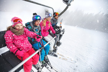 Family in ski lift going to ski terrain