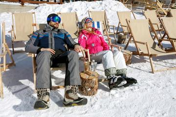 Couple sunbathing on  snowy mountain
