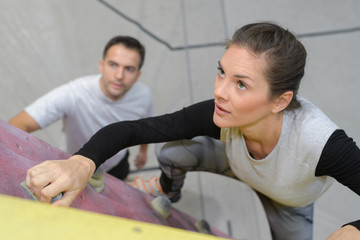 fit woman lclimbing wall at the gym