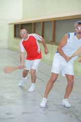 Men playing squash with wooden racket
