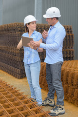 Man and woman in conversation next to stack or reinforcement bars