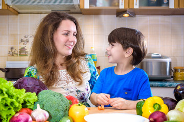 The young cook mother standing with her little son in the kitchen and salting vegetables