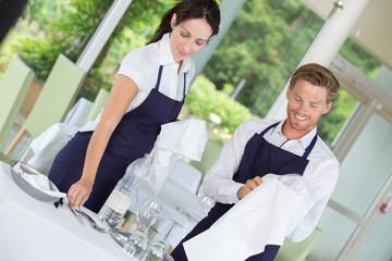 waitress and waitress preparing restaurant table
