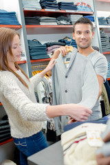 Couple in clothes shop, lady holding man's cardigan