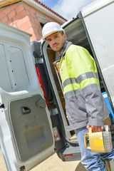 portrait of worker while standing by van