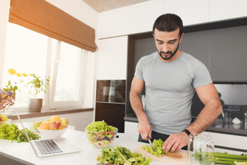 A sporty man is preparing a salad in the kitchen. He cuts the leaves of the lettuce and puts them in a jar.