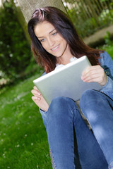 pretty student using digital tablet outdoors