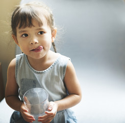 Litlle girl drinking a glass of milk