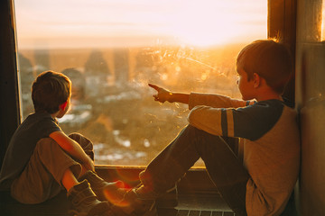 children sitting on the windowsill. Two boys looking out the window at the top of a skyscraper