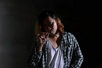 Low key image of androgynous beautiful young man as a beautiful woman in dark background.