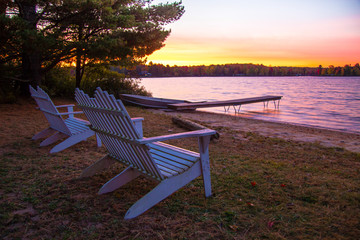 Foto op Plexiglas Meer / Vijver Summer Vacation At The Lake. Sunset over a lake with a row of Adirondack Chairs, dock and aluminum rowboat.