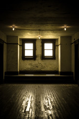 Empty Room. Bare light bulbs and hardwood floor in outdated and dreary empty room.