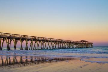 Myrtle Beach Ocean Pier Background. Sunset colors on the coast of Myrtle Beach, South Carolina with as waves crash on the Atlantic coast beach. Wall mural