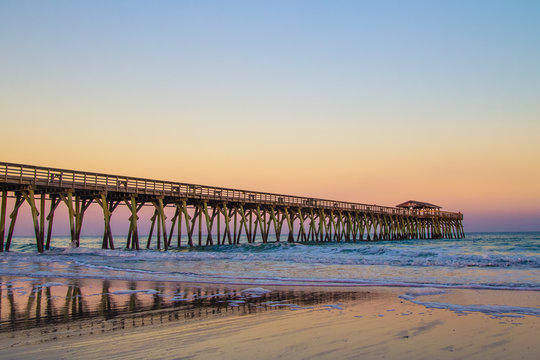 Myrtle Beach Ocean Pier Background. Sunset colors on the coast of Myrtle Beach, South Carolina with as waves crash on the Atlantic coast beach.