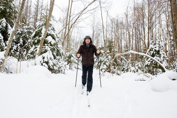 Young man cross-country skiing in the forest