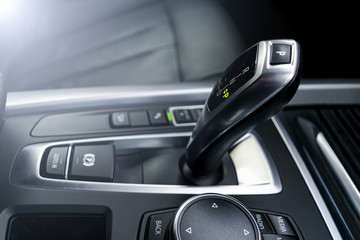 Automatic gear stick (transmission) of a modern car, multimedia and navigation control buttons. Car interior details. Transmission shift. Soft lighting
