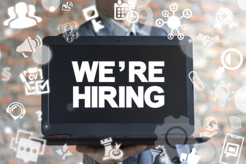 Businessman using virtual interface offers laptop with We're Hiring text. We Are Hiring. Join Our Team Business concept.