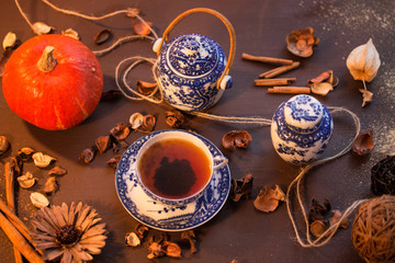 a cup of tea and chineeze crockery and red pumpkin. warm light