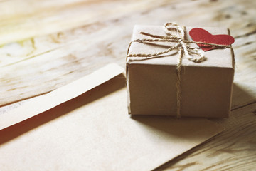 On a wooden table an envelope and a gift box with a heart
