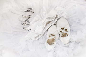 Children's ballet shoes, skirt and hairpins for hair. Still Life with white ballet accessories. Top view.