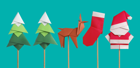 Handmade origami paper craft Santa Claus, green Christmas trees and reindeer on light green background
