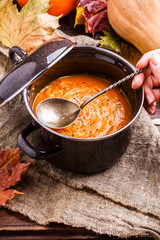 Photo of soup puree in saucepan, pumpkin on linen cloth