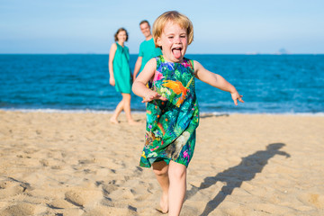 Daughter 4-years-old run away from parents on the beach. Family look