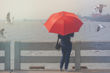 Woman standing on concrete bridge, she holding red umbrella and looking at sea and seagulls flying at Bangpu Recreation Center, Smutprakarn Province, Thailand.