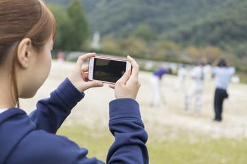 野球の試合をスマホで撮影する野球部マネージャー