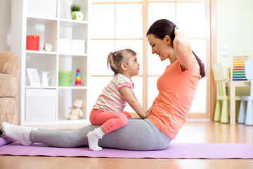 Momr and her child daughter are engaged in fitness, yoga, exercise at home. Kid and woman swing press on stomach.