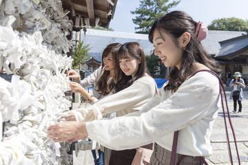 神社へお参りする女性三人組