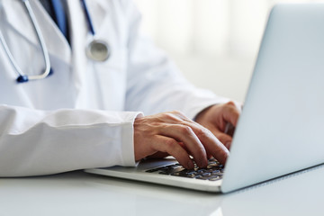 Male doctor working on laptop at clinic