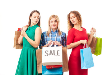 Portrait of three young woman holding bunches of multi-colored shopping bags after sale