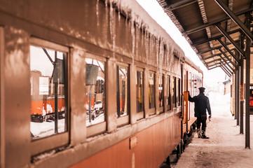 Train conductor of classic old potbelly stove train, Tsugaru railway Goshogawara station, Aomori, Japan.