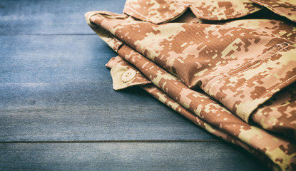 American military digital pattern uniform, folded on wooden background, copy space