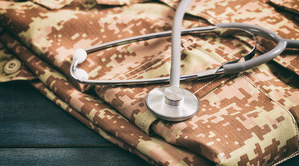 American military digital pattern uniform and stethoscope on wooden background