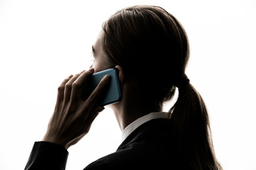 Silhouette of young caucasian woman using smart phone.