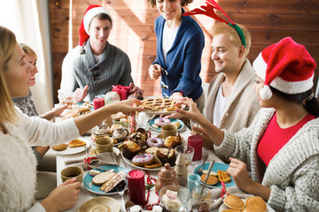 Hungry girls taking pieces of sweet homemade pie by festive table