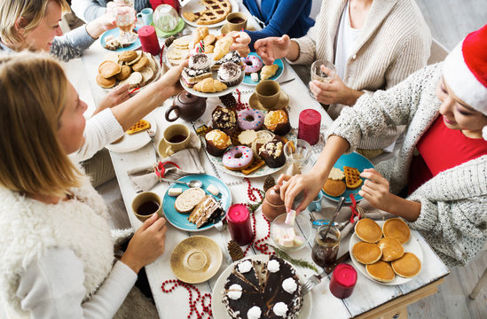 Young friends gathered by xmas dinner having tea with tasty homemade desserts and pastry