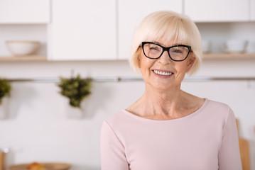 Joyful nice woman standing in the kitchen
