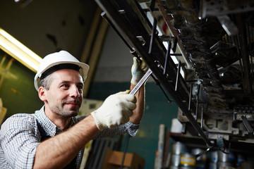Contemporary industrial repairman fixing detail of huge machine