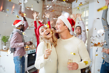 Laughing girl and her boyfriend in sweaters and caps enjoying xmas party with friends