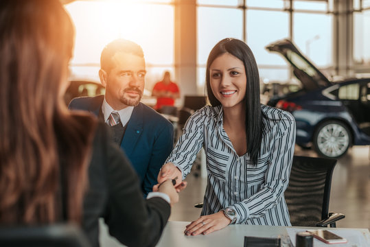 Smiling woman customer shaking hands with car dealer.