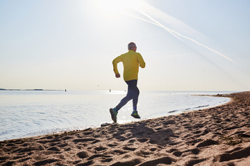 Active pensioner running along coastline on sandy beach in the morning
