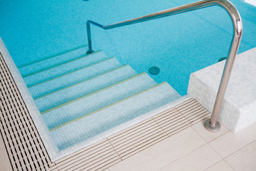 Steps seen in blue water in swimming pool