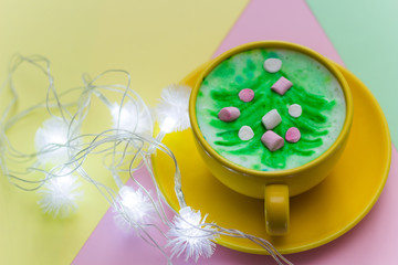 cappuccino with painted christmas tree in a bright yellow mug on bright yellow,pink and green background.