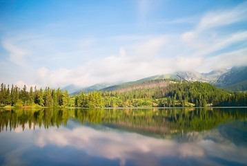 Vysoke Tatry, Strbske Pleso, Slovakia - mirroring trees on the water surface with a diving platform. Beautiful Slovakia. A long time.